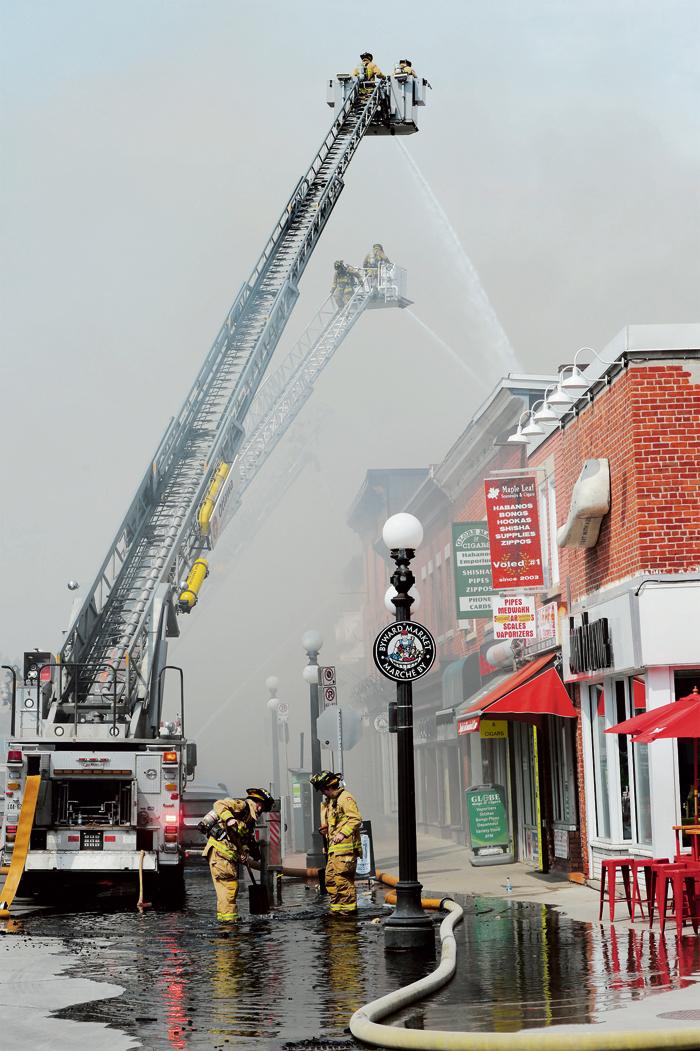 ■消防员架起云梯,向火场射水。加通社