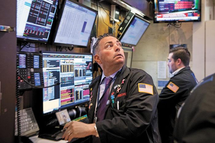 中国宣布对美采取反制措施,美股三大指数13日暴跌。图为纽约证券交易所的交易员紧盯大盘。彭博社