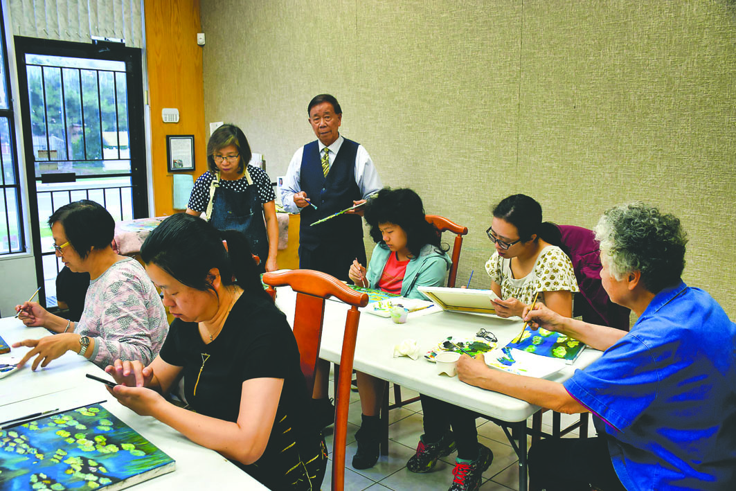 """美术会会长伍川宇(左4)在""""暑期学堂""""教授油画,学生正专心绘画。"""