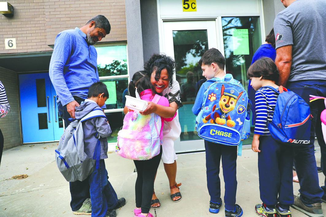 全省200万位中小学生,昨日开学,一位幼稚园教师(左四)在学校门外,拥抱学生,欢迎他们回到校园。星报