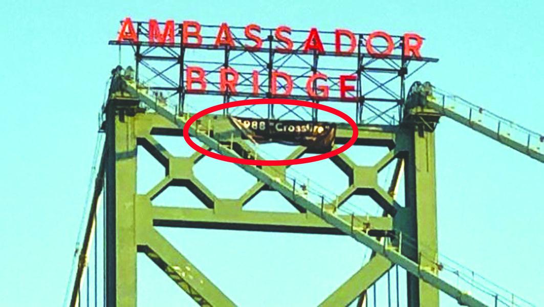 一名青年爬上大使桥顶,悬挂一幅宣传其乐队的横额(红圈示)。 CTV