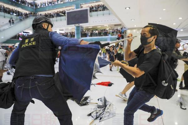 A policeman scuffles with a protester inside a mall in Sha Tin District in Hong Kong, Sunday, July 14, 2019. Police in Hong Kong have fought with protesters as they broke up a demonstration by thousands of people demanding the resignation of the Chinese territory's chief executive and an investigation into complains of police violence. (AP Photo/Kin Cheung)