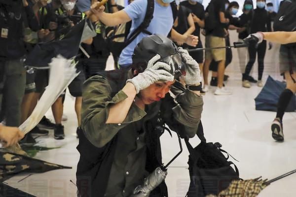 A policeman reacts as he attack by protesters inside a mall in Sha Tin District in Hong Kong, Sunday, July 14, 2019. Police in Hong Kong have fought with protesters as they broke up a demonstration by thousands of people demanding the resignation of the Chinese territory's chief executive and an investigation into complains of police violence. (AP Photo/Kin Cheung)