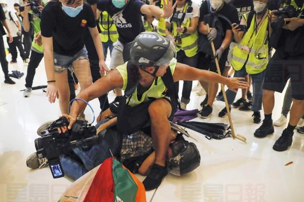 A journalist tries to protect a policeman lies on the floor after he being attacked by protesters inside a shopping mall in Sha Tin District in Hong Kong, Sunday, July 14, 2019. Police in Hong Kong have fought with protesters as they broke up a demonstration by thousands of people demanding the resignation of the Chinese territory's chief executive and an investigation into complains of police violence. (AP Photo/Kin Cheung)