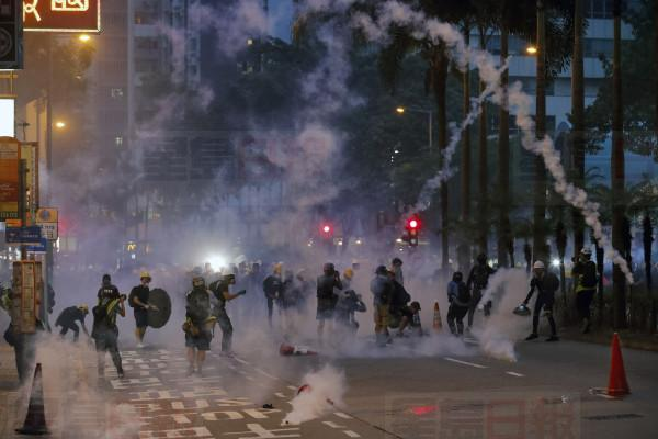 Protesters react with tear gas canisters fired by riot policemen on a street in Hong Kong, Sunday, Aug. 11, 2019. Police fired tear gas late Sunday afternoon to try to disperse a demonstration in Hong Kong as protesters took over streets in two parts of the Asian financial capital, blocking traffic and setting up another night of likely showdowns with riot police. (AP Photo/Vincent Thian)