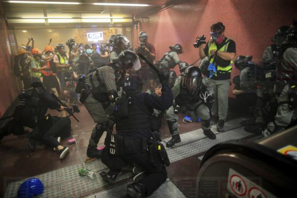 Policemen charge and arrest protesters inside the Tai Koo MTR station during the anti-extradition bill protest in Hong Kong, Sunday, Aug. 11, 2019. Police fired tear gas Sunday inside a train station and in several other Hong Kong neighborhoods where protesters occupied roads in another weekend of anti-government demonstrations. (Jeff Cheng/HK01 via AP)