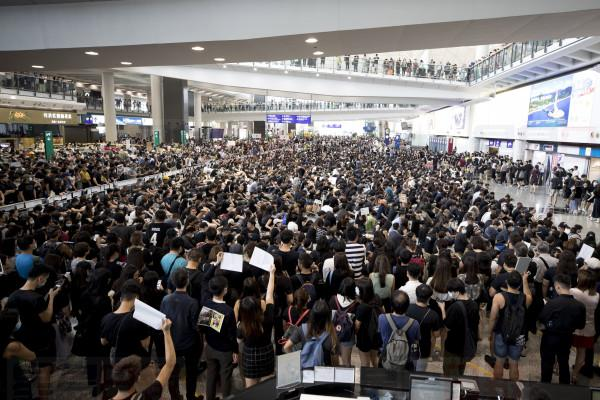 Protesters demonstrate at the airport in Hong Kong, Monday, Aug. 12, 2019. Several thousand people gathered on Monday for a fourth day of protest against a proposed extradition law at Hong Kong's busy international airport. (AP Photo/Vincent Thian)
