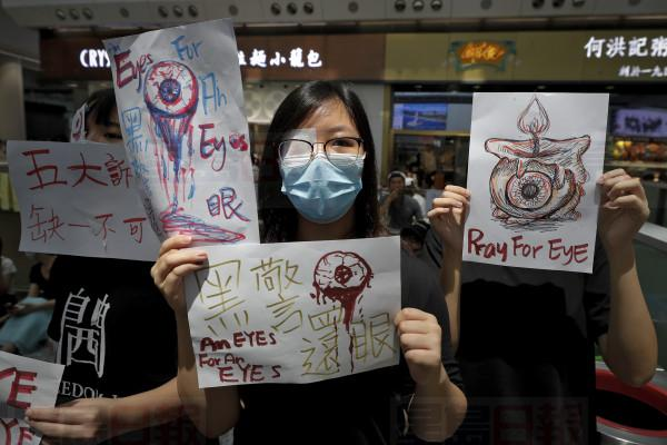 "People hold signs which read "" Black Police, Return eye,"" bottom center, during a protest at the arrival hall of the Hong Kong International airport in Hong Kong, Monday, Aug. 12, 2019. It is reported that police shot a woman in the eye with a projectile Sunday night during confrontations between protesters and police. (AP Photo/Vincent Thian)"